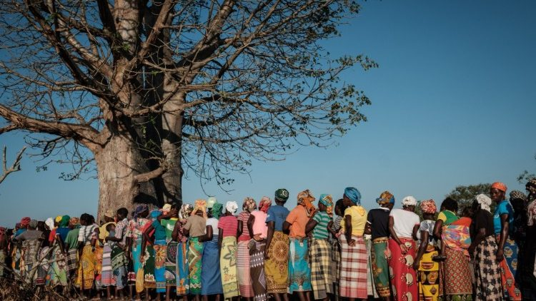 In Mozambique women wait in line to receive relief supplies after Cylone Idai