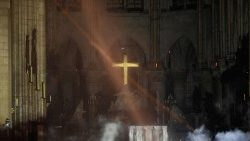 Smoke rises around the main altar and cross inside Paris' Notre Dame Cathedral