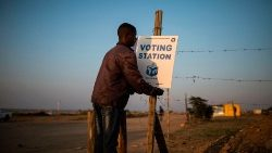 A local resident hangs a sign ahead of elections in an informal settlement on the outskirts of the northern South African city of Polokwane