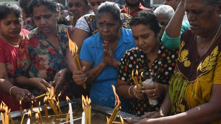 Fiéis católicos cingalesesa acendem velas diante da Igreja de Santo Antônio, em Colombo