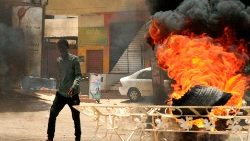 A Sudanese protester walks past a burning tire on a Khartoum street