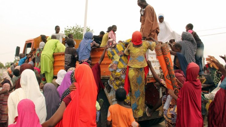 Internally displaced people try to climb a lorry to protest against food shortages, Maiduguri, Nigeria