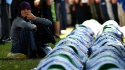 A Bosnian Muslim woman mourns by the caskets of 33 newly identified bodies of the 1995 Srebrenica massacre before their inhumation