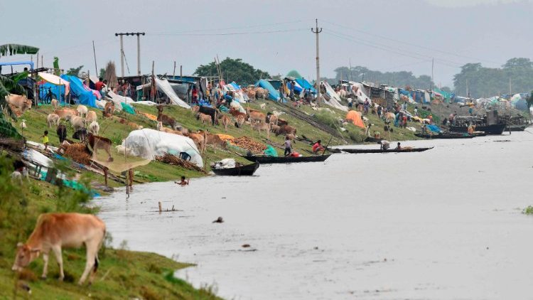 Flood affected villagers in north-east India's Assam state take shelter on an embankment.