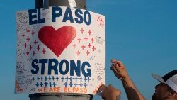 A coach in El Paso, Texas, hangs a sign at a makeshift memorial