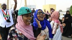 Sudanese women and men celebrate the signing of the power-sharing agreement