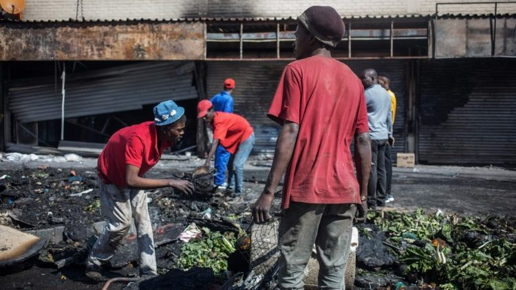 People rummage through looted foreign-owned shops in Alexandra Township, Johannesburg