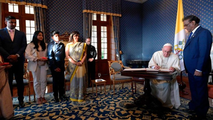 Pope Francis signs the guestbook prior to his meeting with government authorities
