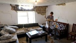 A lady removes a small table from her damaged house in the village of Zhurje near Tirana