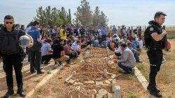 People take part in a funeral for a Kurdish baby killed by artillery fire in Syria