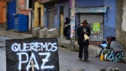 "Bolivians resume daily life next to a sign reading ""We want peace"" in a street of La Paz"
