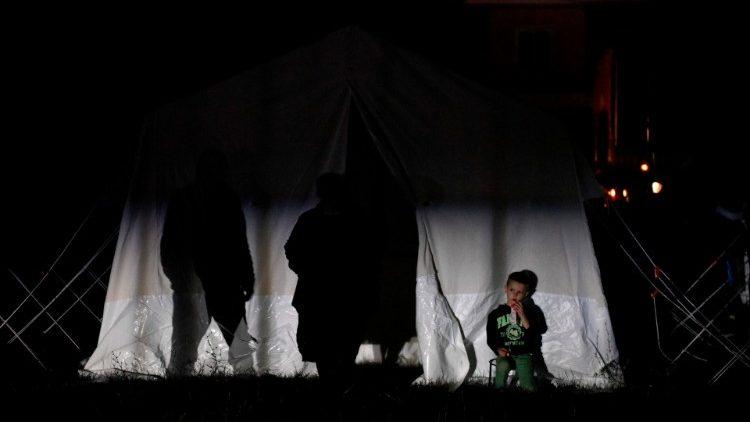 Menino albanês em frente a uma tenda em Thumane, nordeste da capital Tirana