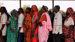 Displaced persons wait in line to receive essentials from an emergency shelter