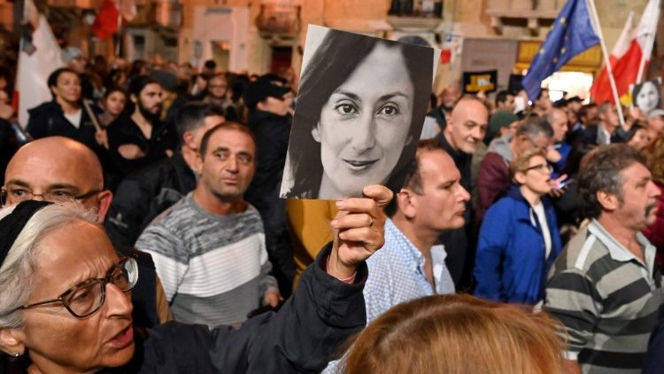 Maltese citizens hold placards of Daphne Caruana Galizia during a protest