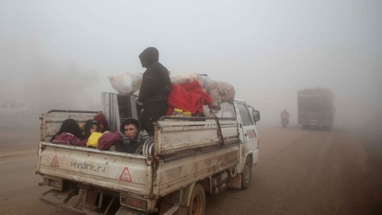 Syrians carrying their belongings drive towards the northern areas of Syria's Idlib province