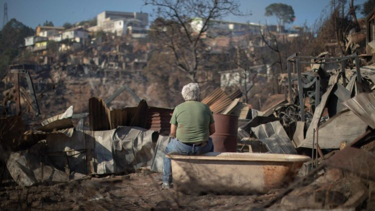 A man looks at the destruction caused by a forest fire in Valparaiso, Chile
