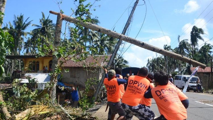 Workers pull a fallen electric pylod after Typhoon Phanfone