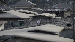 Residents in Laurel town in the Philippines clean the roofs of their homes covered with volcanic ash.