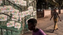 Guineans in Conakry walk in front of posters advertising the Referendum
