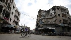 A boy rides his bicycle in front of damaged buildings in the northwestern Syrian city of Idlib