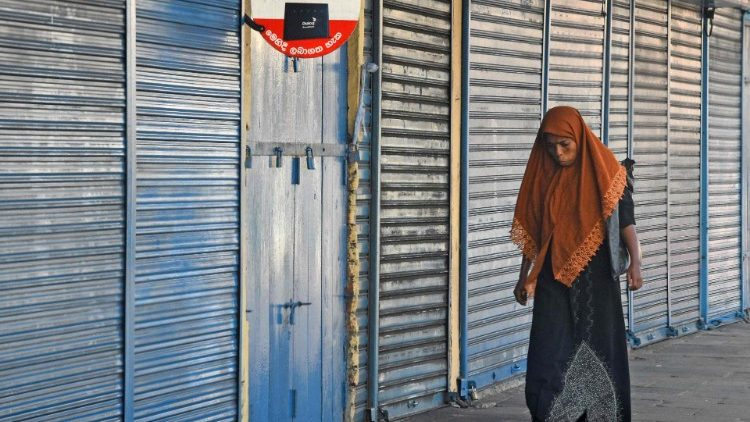 A woman walks next to closed shops in Sri Lanka's capital Colombo