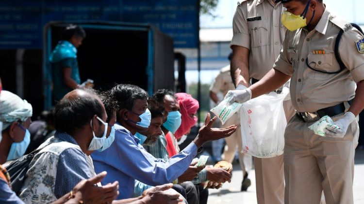 Police distribute food to homeless people during lockdown in India