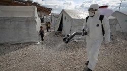 A sanitation worker disinfects a camp for displaced Syrians in Idlib