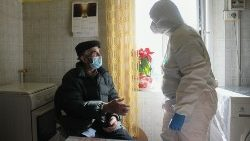 A nurse in PPE assisting an elderly man