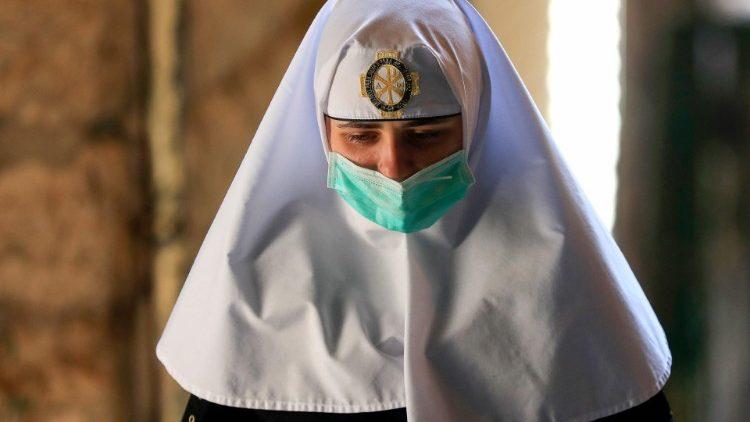 Religiosa em Jerusalém protegida por máscara
