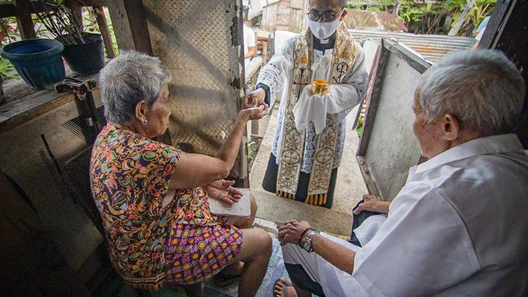 Un couple de personnes âgées recevant la communion à domicile à Borongan, aux Philippines, le 22 avril 2020.