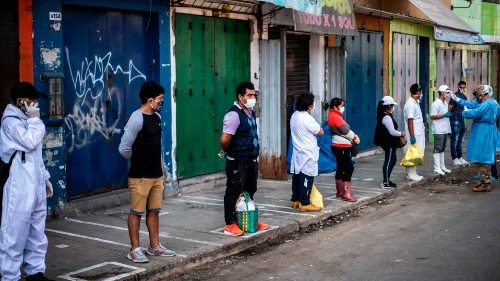 Employees in the food sector wait outside a market in Lima, Peru