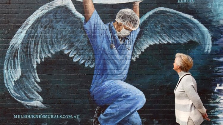 A woman looks at a mural of a nurse with wings  holding a globe on International Nurses Day, Australia