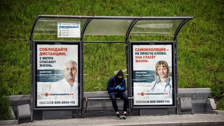 A man at a bus stop decorated with posters promoting social distancing and self-isolation in Moscow, Russia