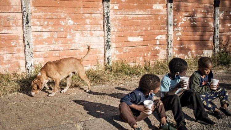 Children in a South African township await food assistance