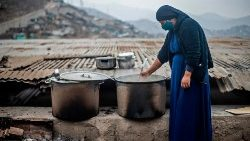 A nun stirs a pot at a soup kitchen in Lima, Peru