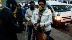 A taxi attendant in SA sprays commuters with hand sanitiser while they queue at a taxi rank