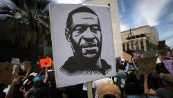 Protesters in Los Angeles hold a sign with an image of George Floyd