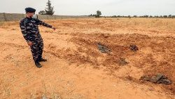 A Libyan soldier stands at the reported site of a mass grave in Tarhuna, Libya