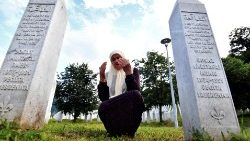 A Bosnian Muslim woman prays between the tombstones of her sons who were killed during the Srebrenica massacre in 1995