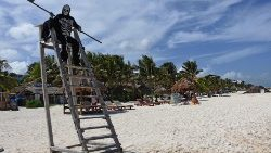 A man dressed as the Grim Reaper warns beachgoers in Mexico to return home