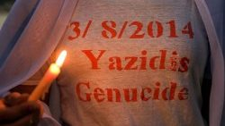 Iraqi Yazidis mark a candlelight vigil recalling the massacre of their community by IS in 2014