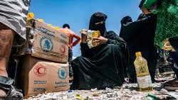 A woman holding bottles of sunflower oil distributed as part of food aid to a displaced persons camp in northeastern Syria (file photo)