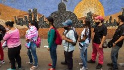 People line up to board a bus next to a mural depicting the National Assembly building in Caracas ahead of parliamentary elections