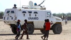 Sudanese children walk past an amoured vehicle of the UN-AU peacekeeping mission in Darfur