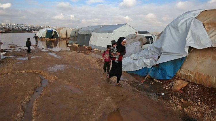 A Syrian woman walks in a camp in Idlib province