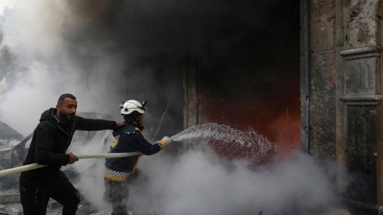 Rescue workers try to extinguish a fire caused by an explosion in the town of Azaz, Syria