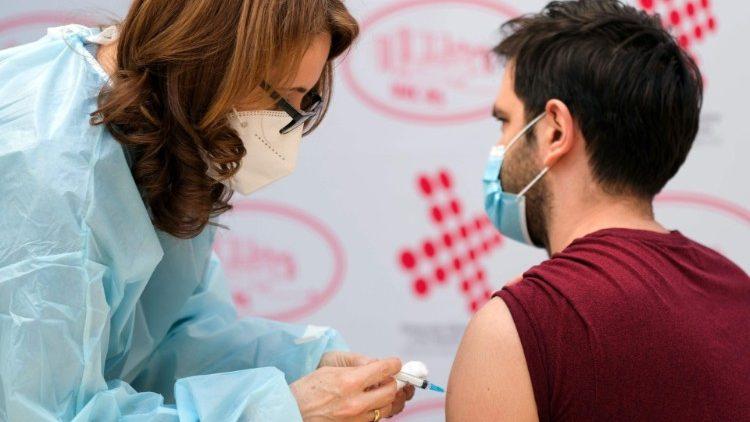 A health worker in Bosnia receives a Covid-19 vaccine