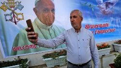 "An Iraqi citizen takes a ""selfie"" against a banner welcoming Pope Francis"