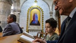Iraqi Christians attend a prayer service at the Syriac Catholic Church in Qaraqosh