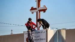 Christians in Iraq repair a cross in Qaraqosh, in Nineveh province